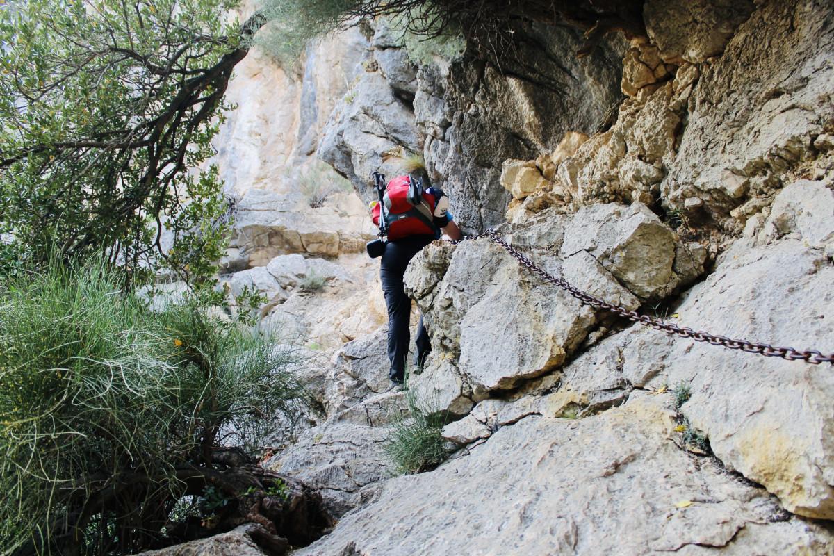 Via de kettingen van de klettersteig hijsen we ons enkele tientallen meters naar boven. Foto: Pauline van der Waal