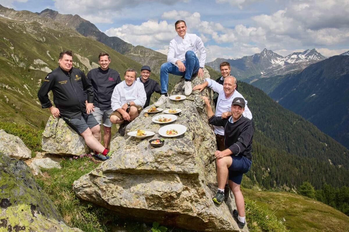Zes sterrenchefs met hun gerecht buiten in de bergen