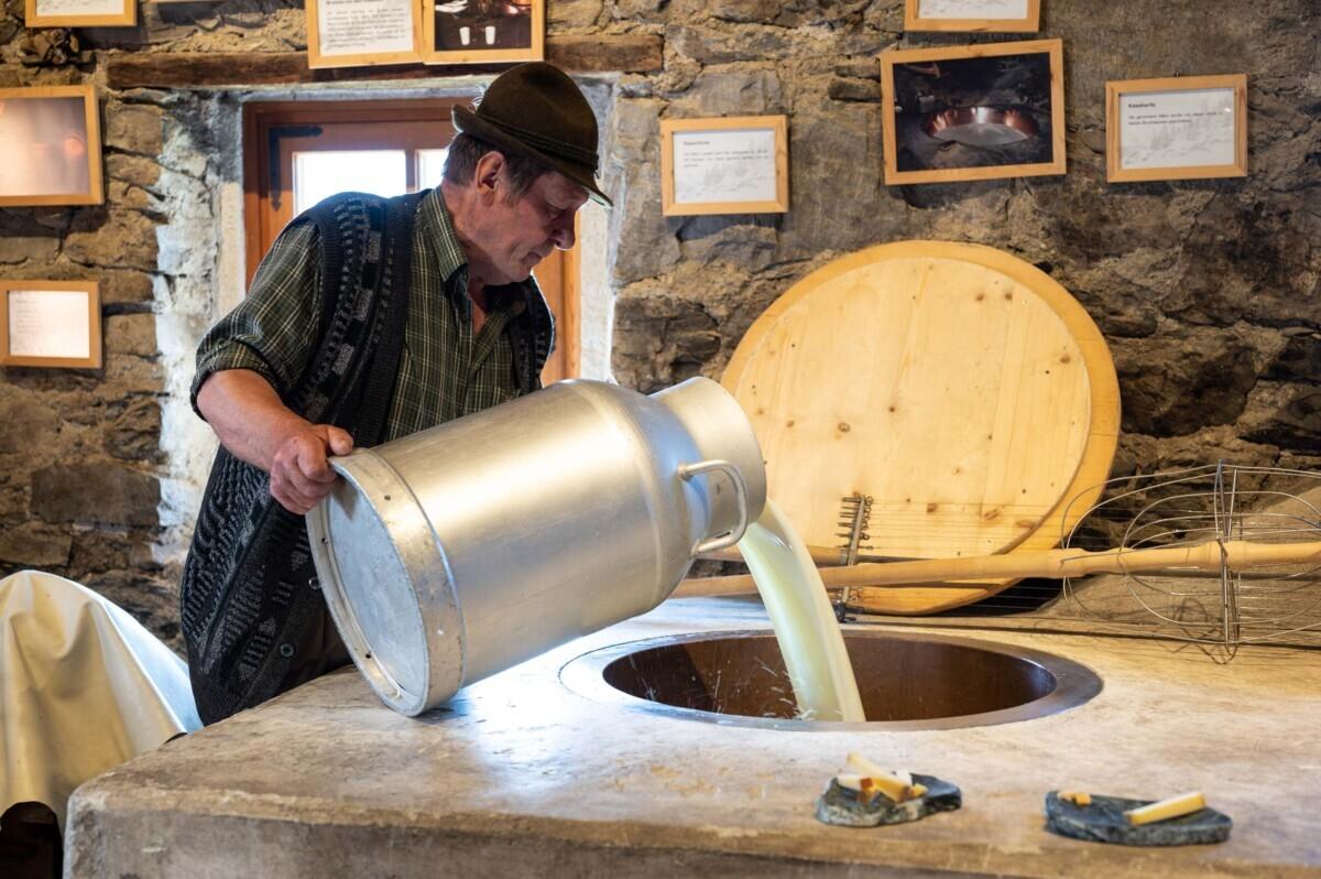 Boer schenkt melk in kaasmaker